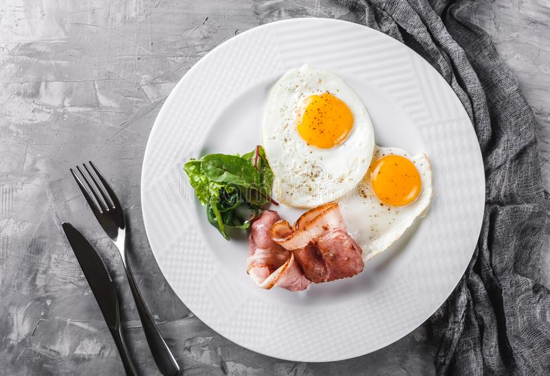 Breakfast, fried eggs, bacon, prosciutto, fresh salad on plate on grey table surface. Healthy food, top view, flat lay.  stock photography