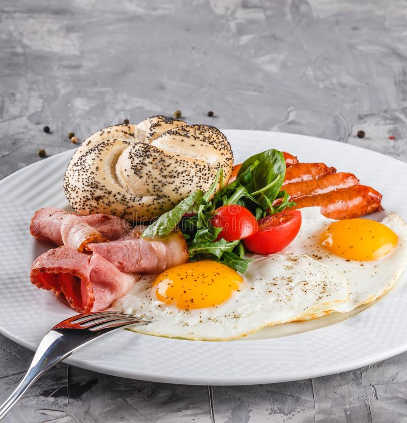 Breakfast, fried eggs, bun, sausage, bacon, prosciutto, fresh salad on plate on grey table surface. Healthy food, top view, flat. Lay stock photo