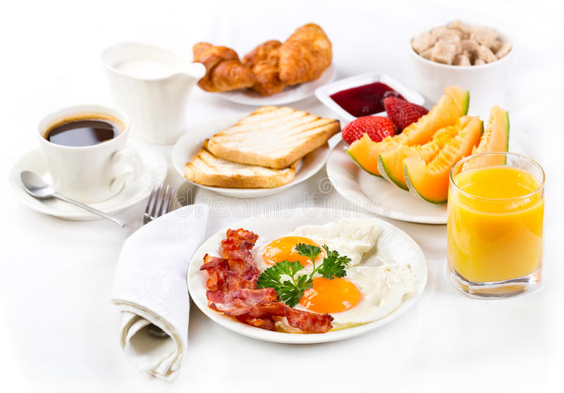 Breakfast. With fried eggs, coffee, orange juice, croissant, toasts and fruits stock image