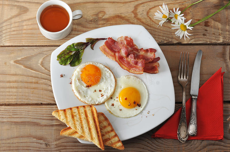 Breakfast - fried eggs, toast, bacon and tea and chamomile on wooden background. The view from the top stock images