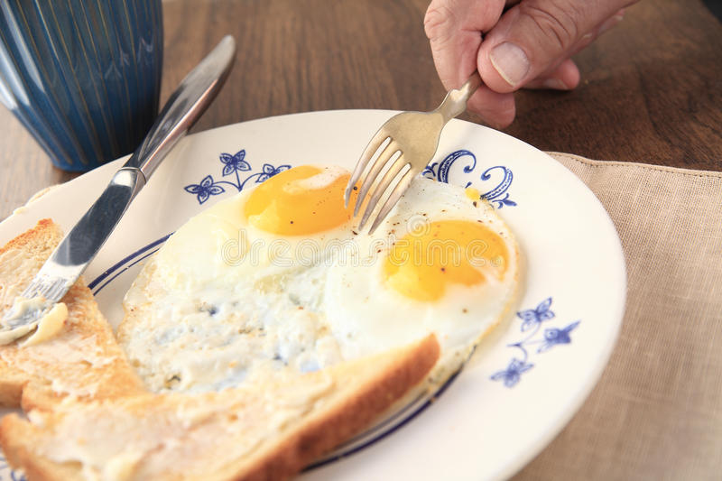 Breakfast of fried eggs and toast. A man with a plate of fried eggs and buttered toast stock images
