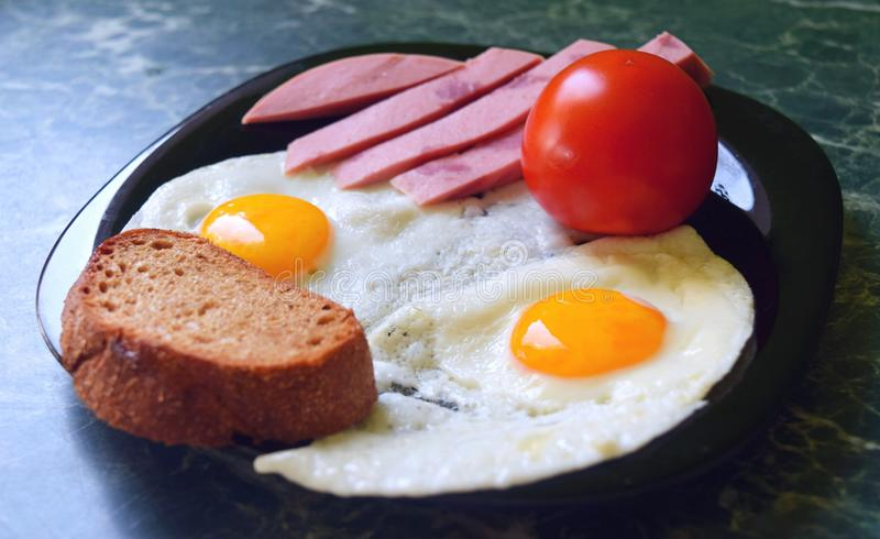 Breakfast. Fried eggs with tomato sausage and bread - from two eggs. stock photography