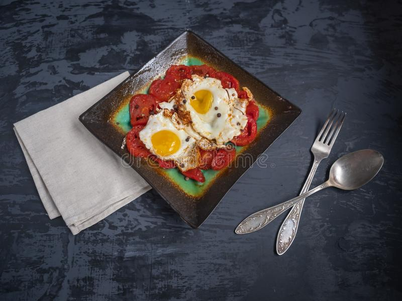 Breakfast of fried red tomatoes and fried eggs royalty free stock photos