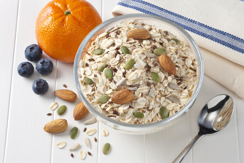 Breakfast Fruit Cereal Fiber Grains. A bowl full of muesli breakfast cereal, with oats, almonds, wholegrains and fruit on a white background stock photography