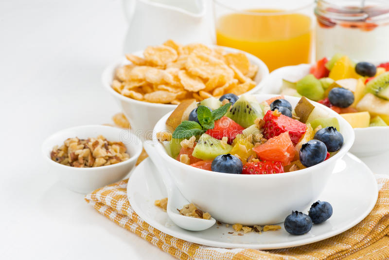 Breakfast with fruit salad and corn flakes on white table. Horizontal royalty free stock photography