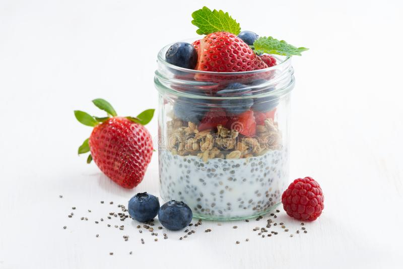 Breakfast in a glass jar, chia with berries and oat flakes. On white table, closeup, horizontal royalty free stock images