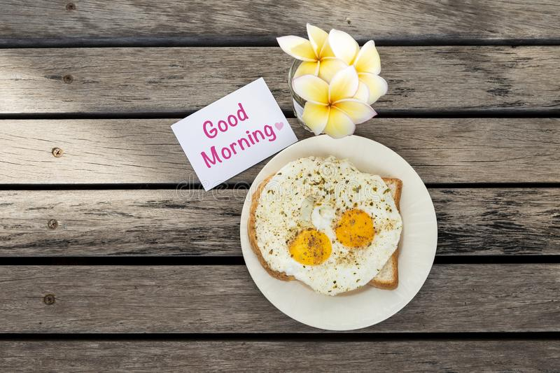 Breakfast with good morning card and beautiful flower on wood background. Fried egg on toast royalty free stock photos