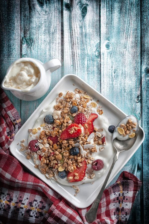 Breakfast granola yogurt, strawberry, blueberries, raspberries on a white plate. stock photos