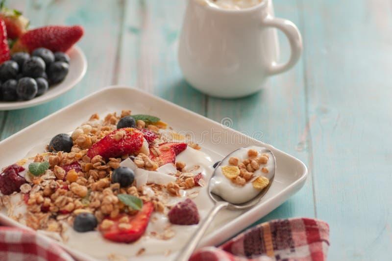 Breakfast granola yogurt, strawberry, blueberries, raspberries on a white plate. royalty free stock photos