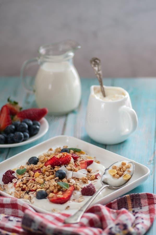 Breakfast granola yogurt, strawberry, blueberries, raspberries on a white plate. royalty free stock image