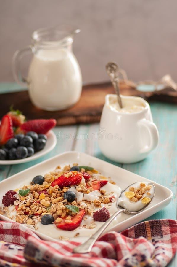Breakfast granola yogurt, strawberry, blueberries, raspberries on a white plate. stock photo