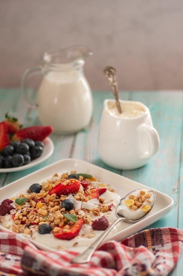 Breakfast granola yogurt, strawberry, blueberries, raspberries on a white plate. royalty free stock images