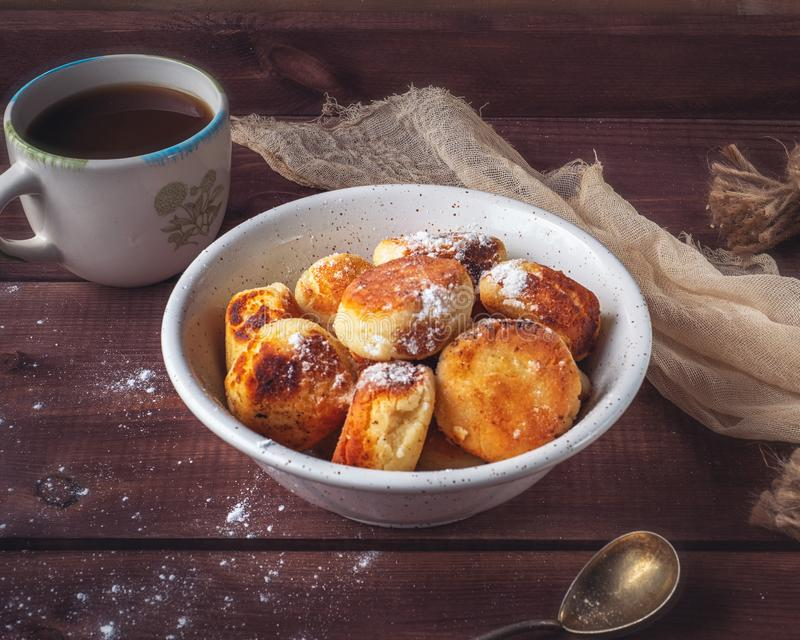 Breakfast with homemade cheesecakes with powdered sugar and tea on a wooden tray. Beige napkin and tea complement the composition stock photos