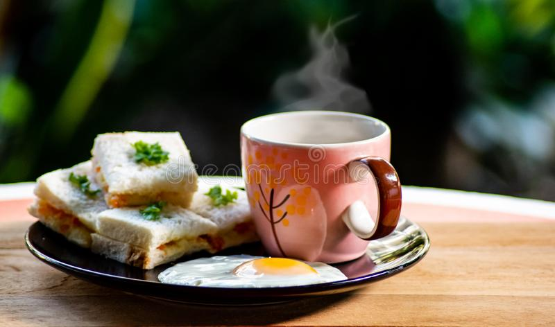 Breakfast homemade,coffee with beautiful white smokey over the cup and small sanwish with fried egg serve. Breakfast homemade,coffee with beautiful white smokey royalty free stock photography