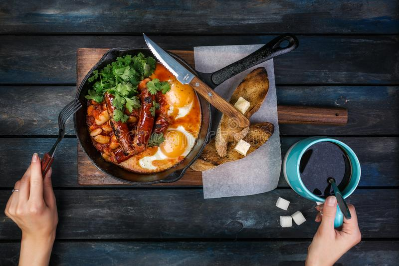 Breakfast in on a hot frying pan with fried eggs, sausages, beans, greenery and toasts. Women`s hands with coffee and. Cutlery. On a colored wooden background stock image