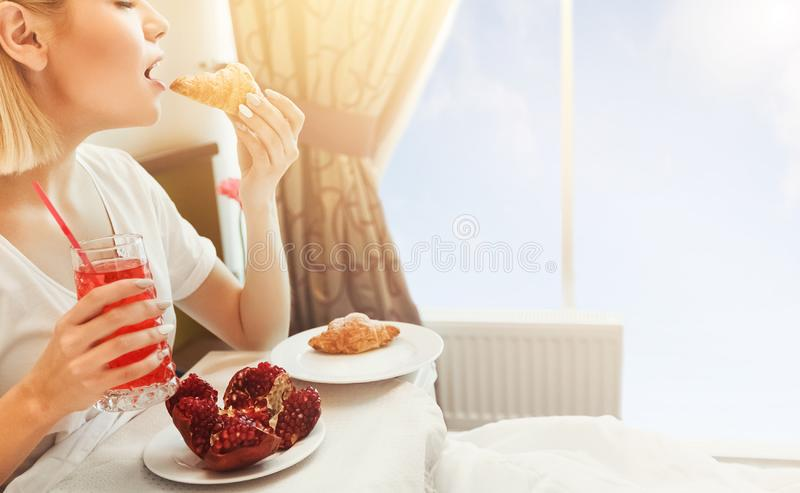 Breakfast In Hotel Room. Woman Eating Croissants and Pomegranate royalty free stock photography