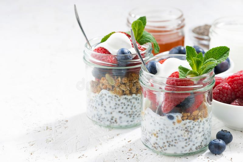 Breakfast in a jar with chia, berries and oat flakes. On white background, horizontal royalty free stock photo