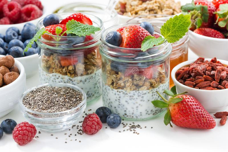 Breakfast in a jar, chia with berries and oat flakes. And ingredients on white table, closeup stock photography