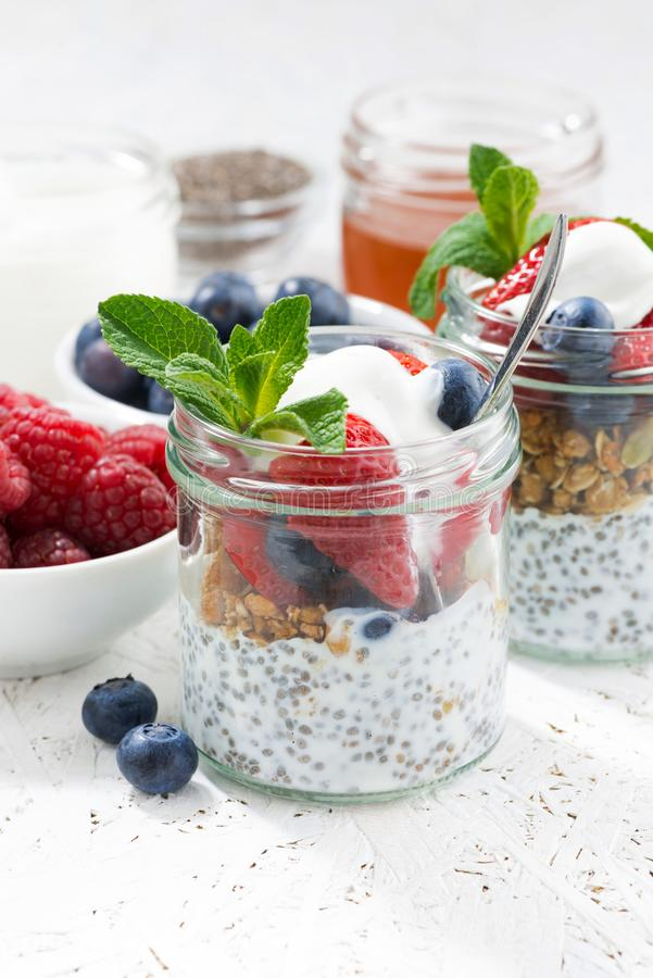 Breakfast in a jar with chia, berries and oat flakes, vertical. Closeup royalty free stock image