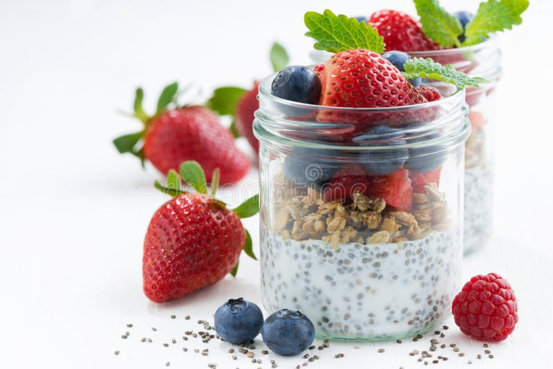Breakfast in a jar, chia with berries and oat flakes. On white table, closeup, horizontal stock photography