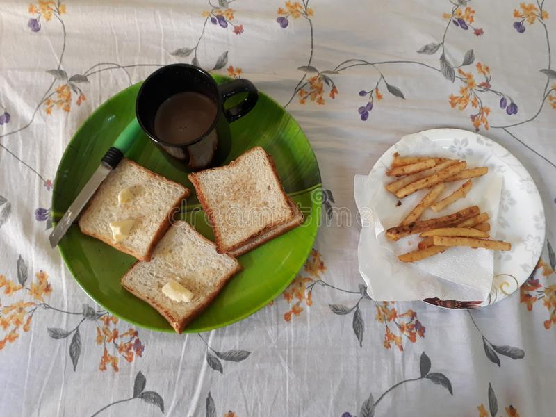 Breakfast. Kept on bed . It consists of bread and butter, french fries and milk with chocolate stock photo