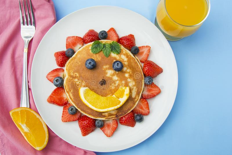 Breakfast for kids. Homemade american pancake sun, with fresh blueberries, strawberries and orange juice. Blue background stock image