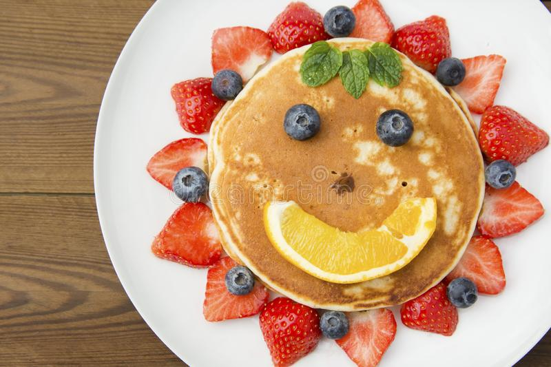Breakfast for kids. Homemade american pancake sun, with fresh blueberries, strawberries and orange juice. Wooden rustic background royalty free stock photo