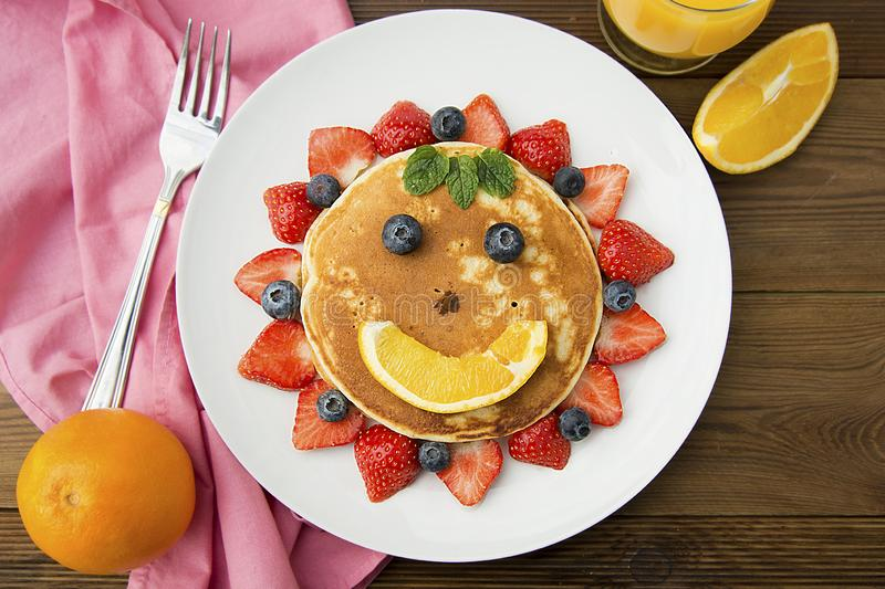 Breakfast for kids. Homemade american pancake sun, with fresh blueberries, strawberries and orange juice. Wooden rustic background. Breakfast for kids. Homemade royalty free stock photos