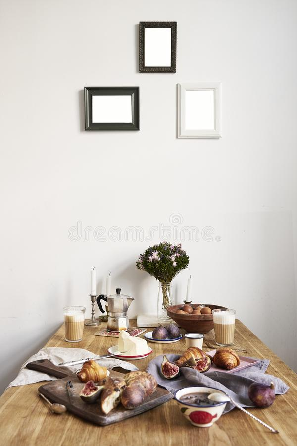Breakfast in kitchen with photo frames on white wall. Croissants, figs, coffee, bread on wooden table background, space for layout royalty free stock photography