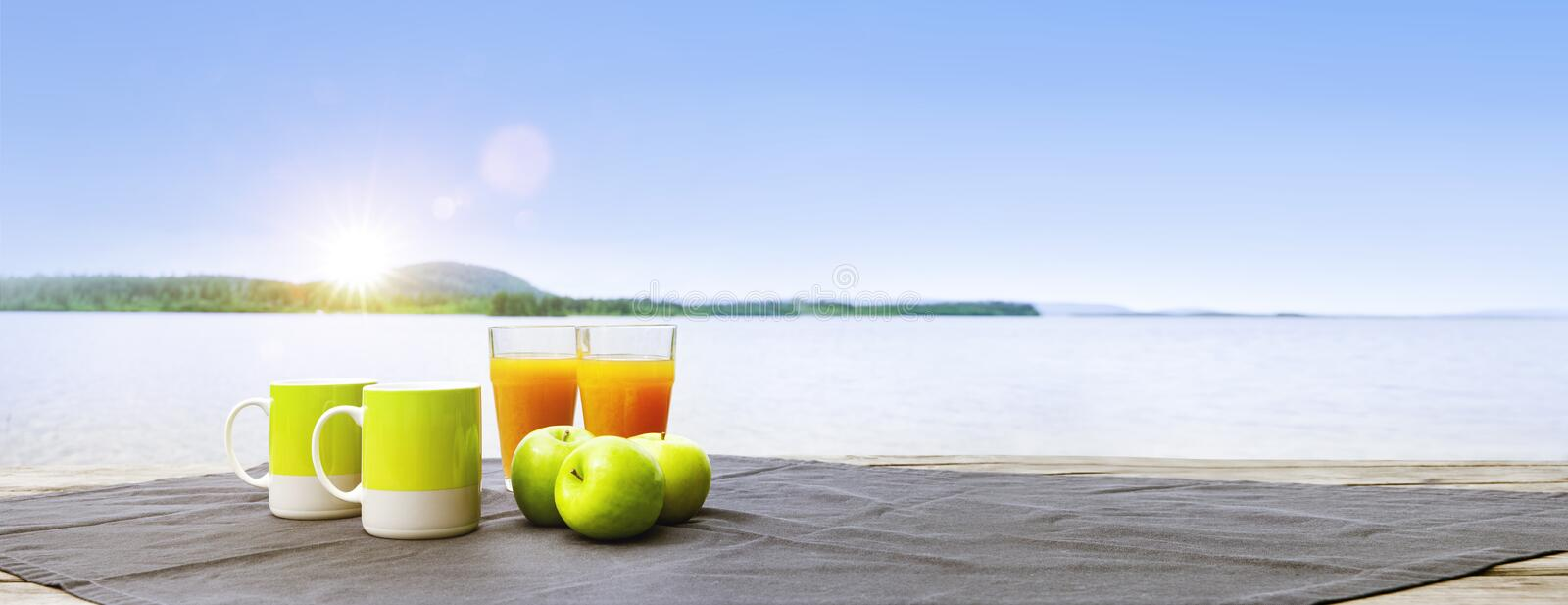 Breakfast at the lake with apples and orange juice. Banner stock images