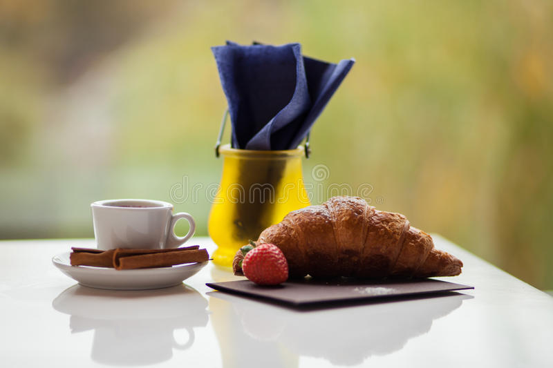 Breakfast. A light breakfast of croissants, decorated with strawberries and a cup of coffee. Mood for the whole day stock image
