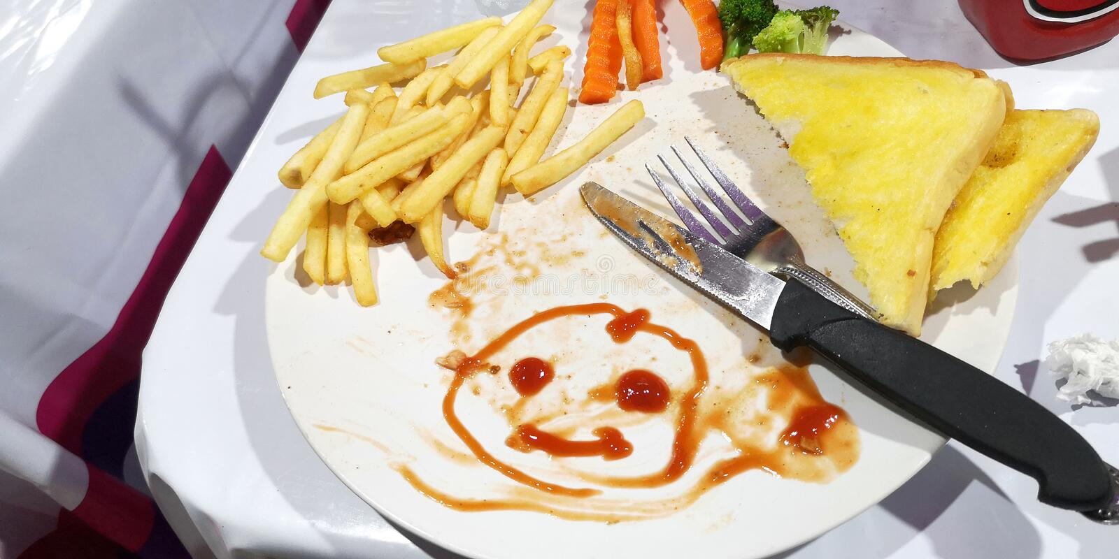 Breakfast or lunch the boy create to drawn tomato sauce cartoon smiling face on his plate white color. Breakfast or lunch the boy he create of art to drawing stock photos