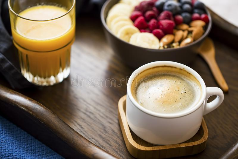 Breakfast meal with cup of coffee, glass of orange juice and a bowl of oatmeal with fresh berries, banana and almonds, healthy stock images