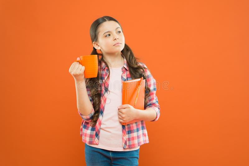 Breakfast the most important meal of the day. Little child having breakfast on orange background. Cute pupil holding stock photos