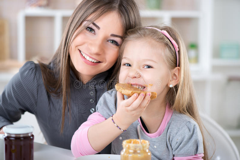 Breakfast. Mother and daughter breakfast in the kitchen. Cute little girl eats bread with peanut butter. Looking at Camera stock photos