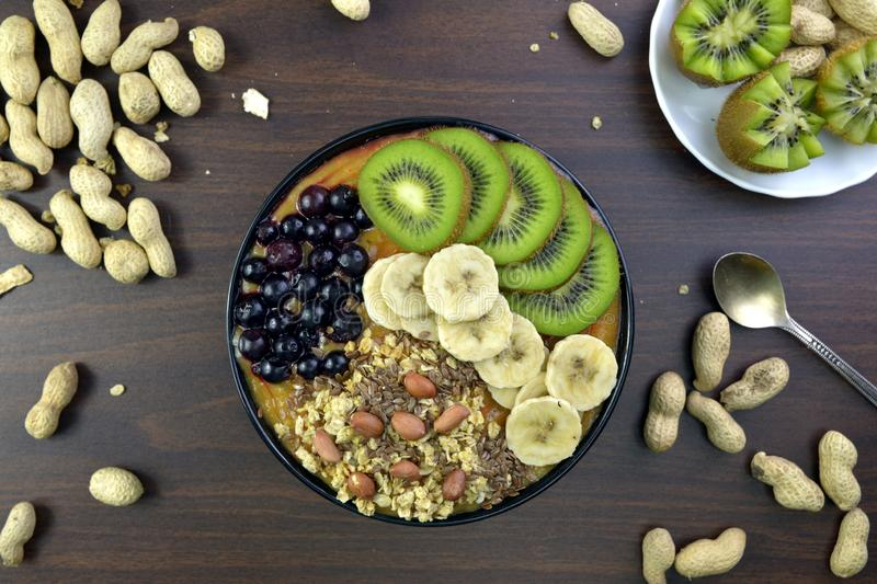 Breakfast with muesli, acai blueberry smoothie, fruits on brown royalty free stock image