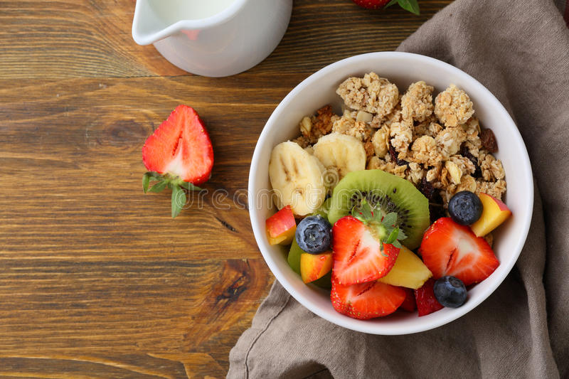 Breakfast muesli with fruits in bowl on wood stock photography