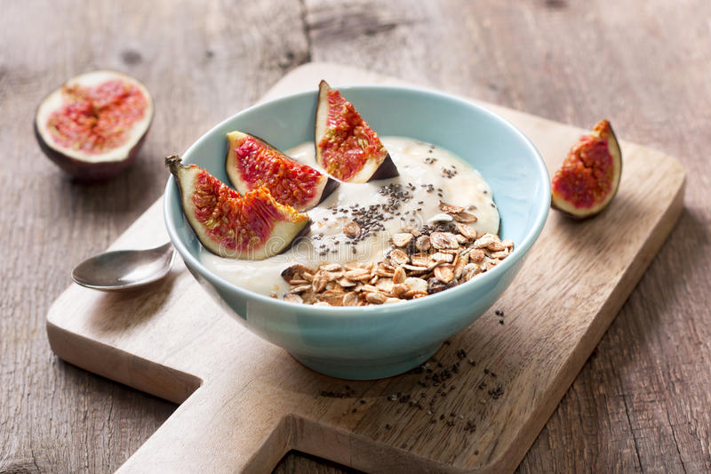 Breakfast with muesli, yogurt, figs. And chia seeds in a blue bowl on a wooden background royalty free stock images