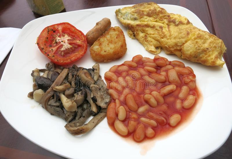 A breakfast of mushrooms, beans, eggs, tomato, sausage and hash browns. stock photo