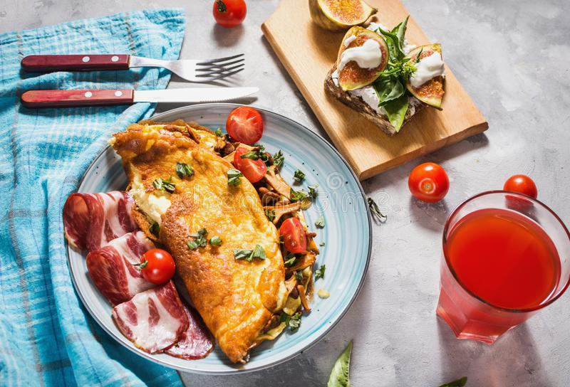 Breakfast mushrooms omelet and sandwich with figs on concrete background. stock photography