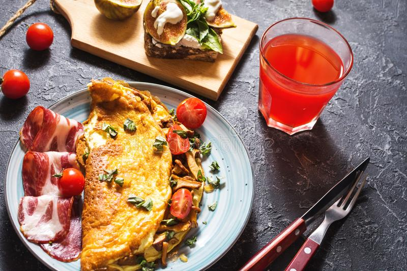 Breakfast mushrooms omelet and sandwich with figs on stone background. stock photos