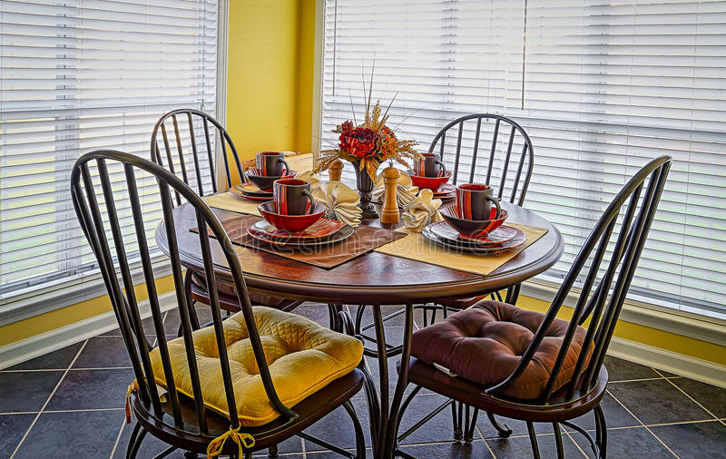 Breakfast Nook. Picture of a warm and inviting breakfast nook with earth tone table décor illuminated by natural light stock image