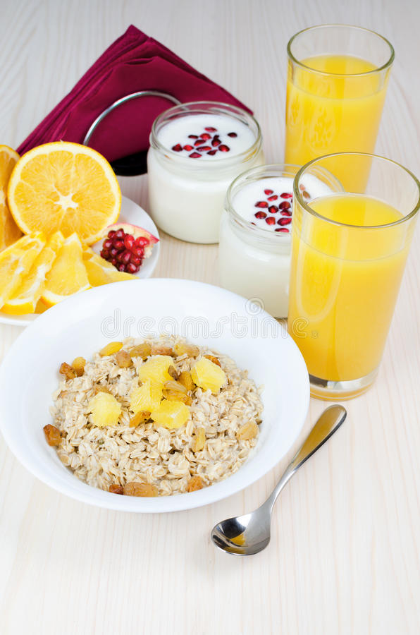Breakfast of oatmeal with raisins and orange royalty free stock image