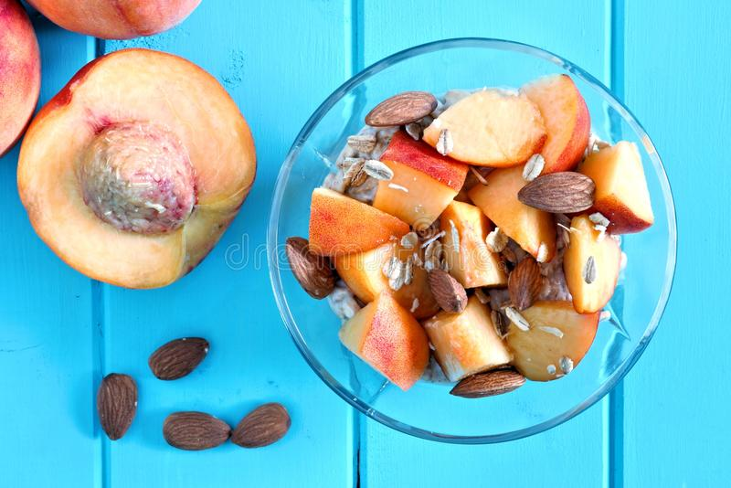 Breakfast oats with peach slices and almonds on blue wood stock photography