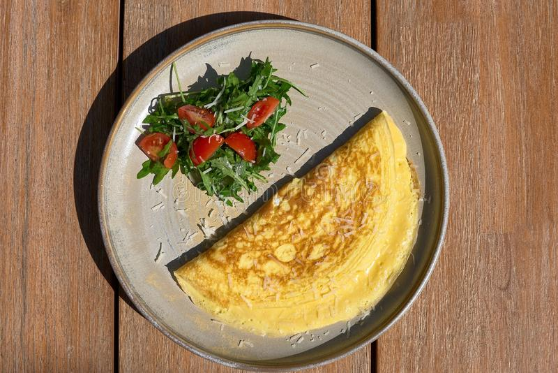 Breakfast. Omelet with tomatoes, arugula, cheese on a blue plate. Frittata - Italian omelette. Top view royalty free stock photos