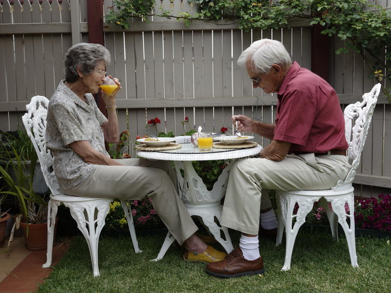 Breakfast Outdoors. An elderly man and woman sit at a small, white wrought iron table as they enjoy breakfast in their garden. The woman is drinking orange juice stock images