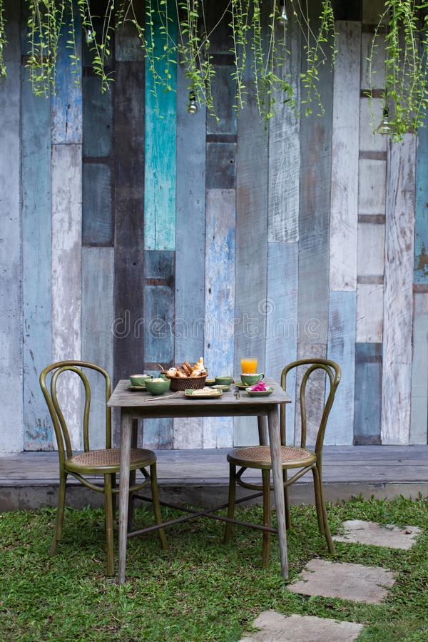 Breakfast outside in garden on vintage wooden table. Textured surface stock photography
