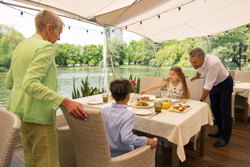 Grandparents coming to grandchildren having breakfast outside royalty free stock images