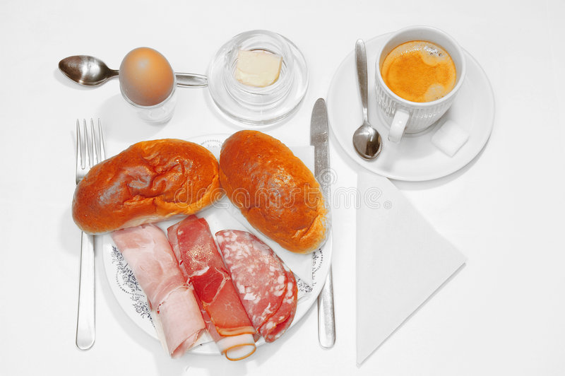 Breakfast over white. A healthy breakfast, daily morning food. Plate with sandwiches, boiled and smoked ham, salami, a boiled egg, butter, coffee isolated stock photography
