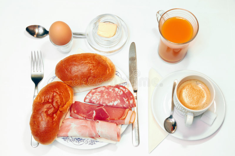 Breakfast over white. Breakfast, daily morning food. Plate with sandwiches, boiled and smoked ham, salami, a boiled egg, butter, coffee and fruit juice isolated stock photos